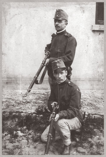 Two Hungarian soldiers in uniform posing with their guns