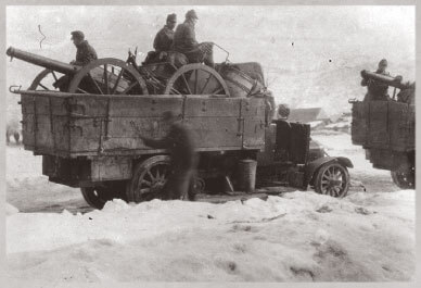 Open truck carrying canon and soldiers in winter
