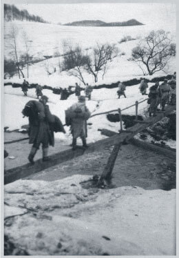 Austro-Hungarian soldiers walking over wooden bridge in winter