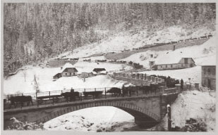 Austro-Hungarian soldiers hauling wagons over an Italian bridge in winter