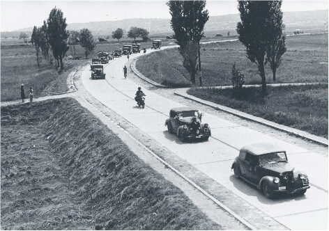Procession of cars and trucks on a road near Lake Balaton that depicts the invasion of Yugoslavia in 1941
