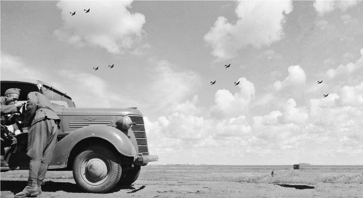 Truck and two soldiers by the roadside in 1941 with bombers flying overhead