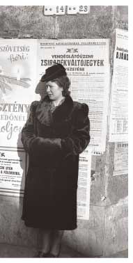 Hungarian woman in fur coat flanked by anti-Semitic propaganda