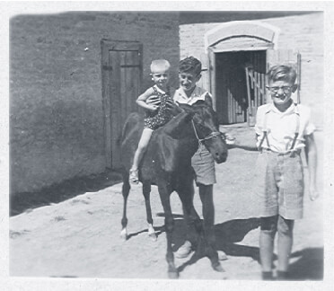 Gyula with cousin Géza with little Miklós in the Fábos family courtyard in 1944