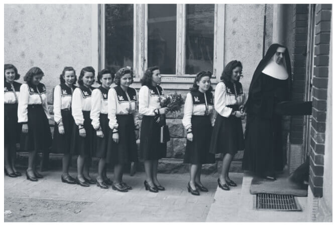 A line of Hungarian Catholic school girls in uniform following a nun into the school building