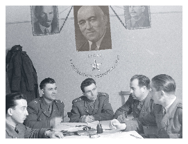 Hungarian policemen meeting under a large portrait of Rákosi