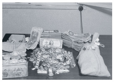 Confiscated dollars, marks, and jewelry resulting from a police search during the Rákosi era