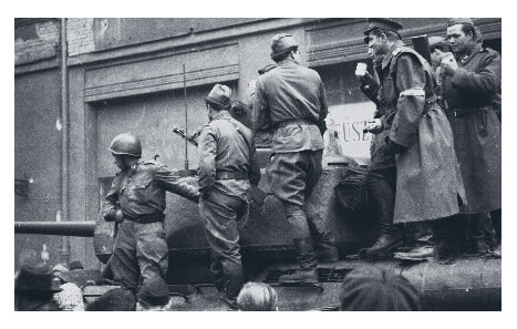 Freedom fighters standing on tanks during the 1956 Hungarian Revolution