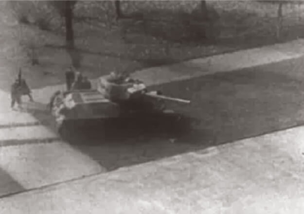 Looped video footage on the left side of the screen showing menacing Soviet tanks advancing from left to right