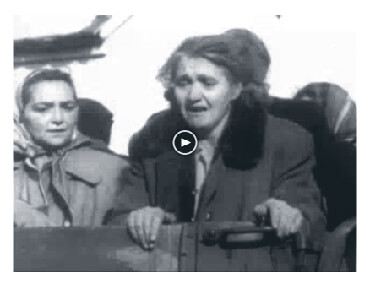 Looped video footage showing an older woman with other Hungarians in the back of an open truck, crying and looking anguished