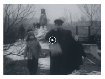 Looped video footage showing weary Hungarian family of four, a father holding the hand of his son followed by a mother holding the hand of their daughter and walking in the snow towards the Austrian border