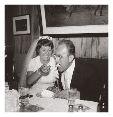 Edith Haüsermann Fabos laughs while feeding cake to Gyula Fábos on their wedding day in 1959