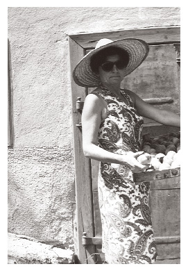 Ari wears a stylish dress with a straw hat and sunglasses while holding a large box of pears in the 1970s