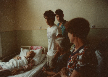 Pista lies in a hospital bed with Leukemia while Laci, Adrian, and Ari stand by in 1983